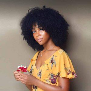 femme noire aux long cheveux crepus avec eau de riz