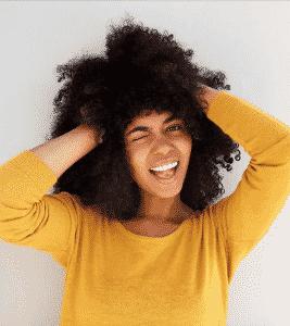 femme souriant mains dans les cheveux boucles